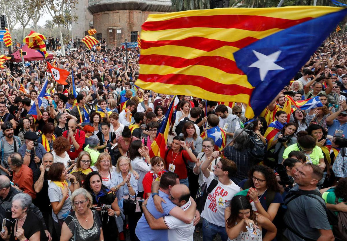 People celebrate after the Catalan regional parliament passes the vote of independence from Spain in Barcelona