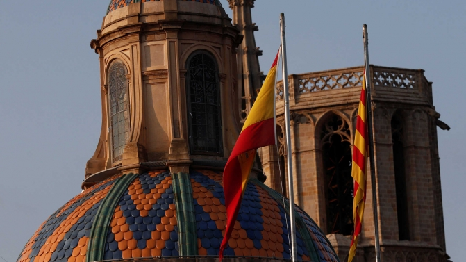 Spanish and Catalan flags are seen atop the Catalan regional government headquarters after the regional parliament declared independence from Spain in Barcelona